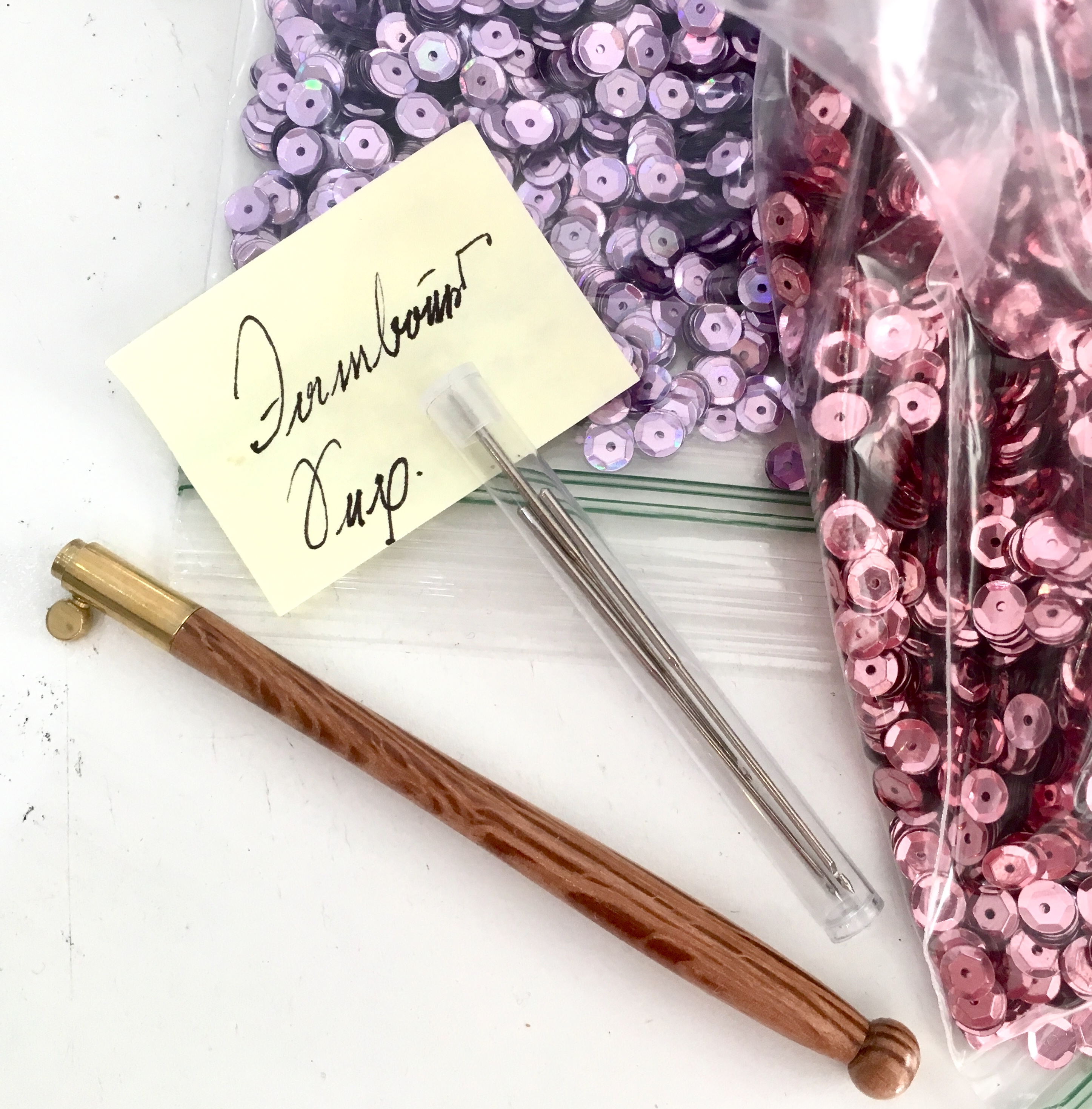 Bags of lilac and dusty rose colored sequins and a tambour hook with needles are waiting to be used in Nathan Perez's Tambour Embroidery Basics class at the Tchad workroom sewing studio in Chicago