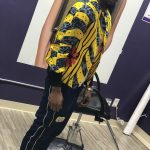 Lamel stands in Foreign lengths hair studio wearing yellow and red wax print bomber made in sewing class at Tchad.