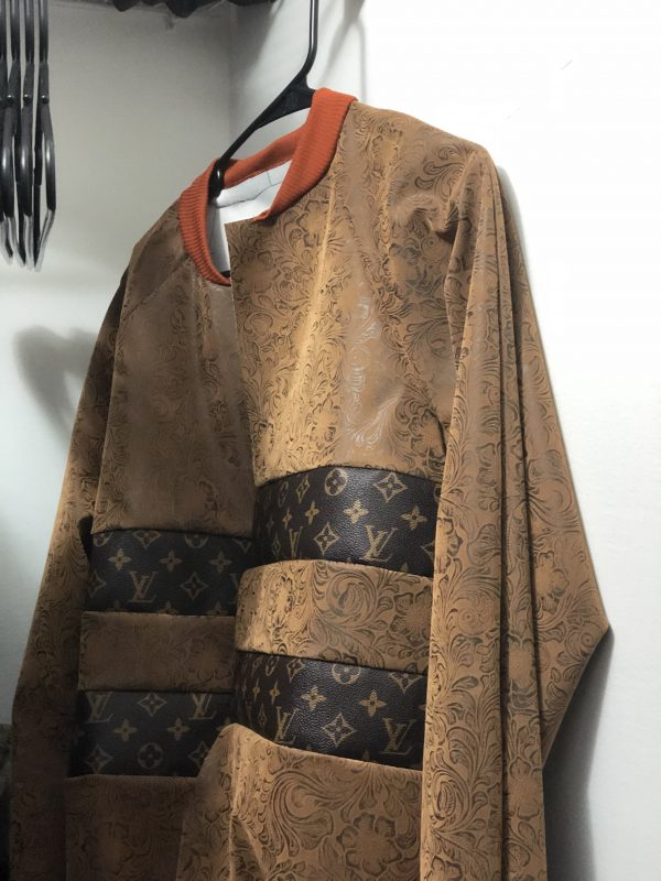 Jacket made of leather and luxury vinyl scraps hanging in closet.