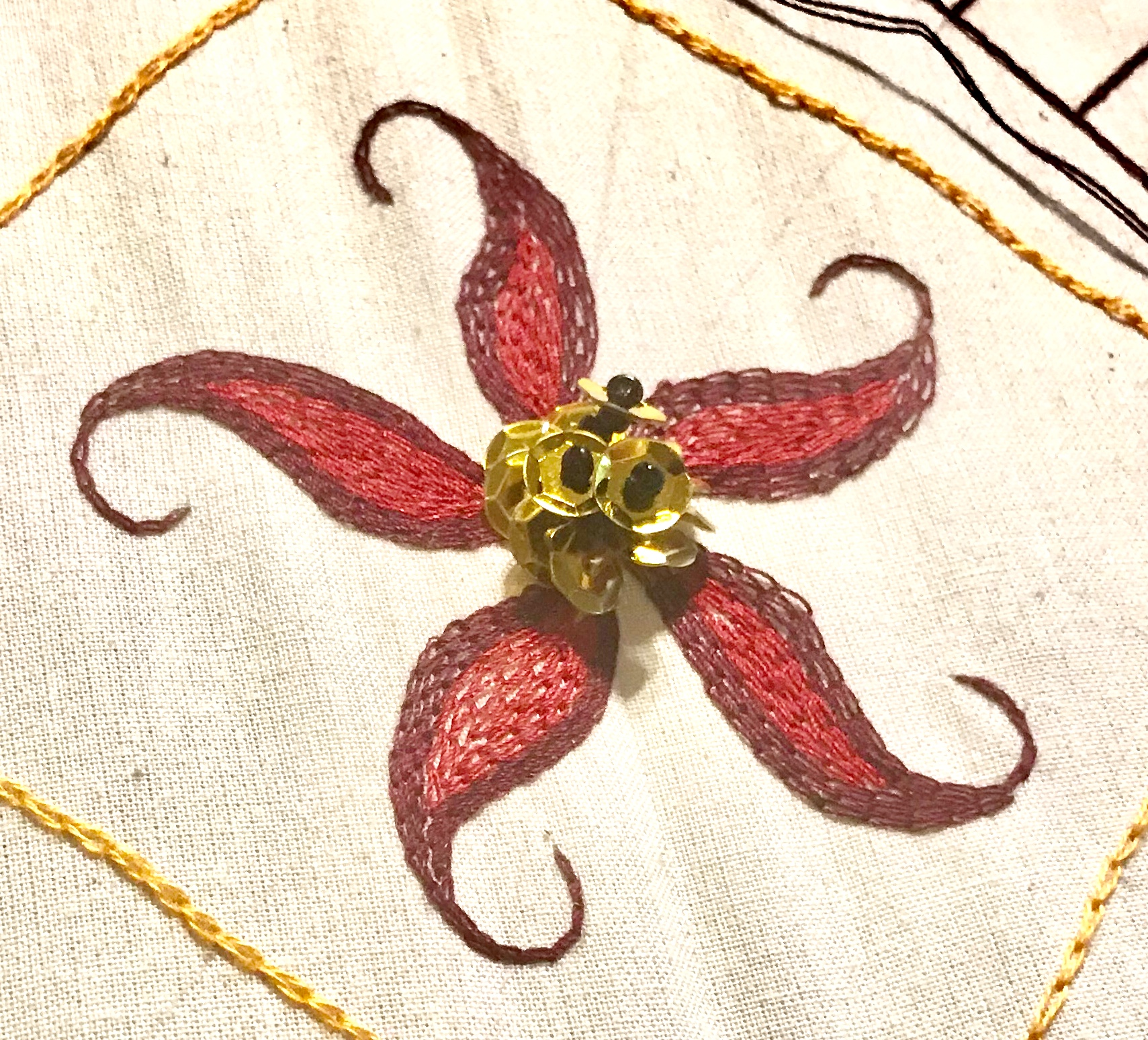 Five-point embroidered flower with beaded center in red and gold by Nathan Perez for the tambour class he will be teaching at Tchad workroom sewing studio in Chicago in August